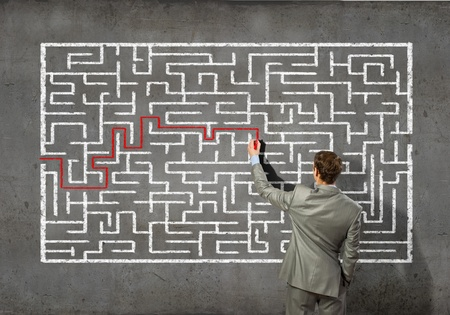 Back view image of young businessman trying to find way out of maze photo