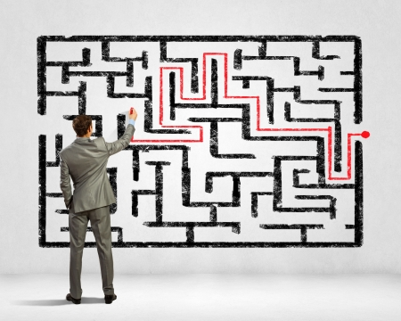 way out: Back view image of young businessman trying to find way out of maze