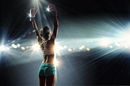 workout gym: Young pretty boxer woman standing in light flashes