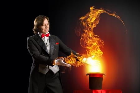 going out: Immagine del mago azienda cappello con fiamme di fuoco e fumi di uscire