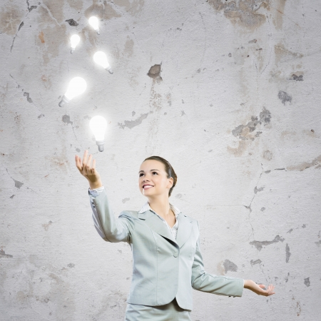 new idea: Image of attractive smiling businesswoman holding light bulbs on hand