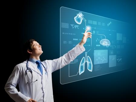 equipos medicos: Joven m�dico masculino icono de tocar en la pantalla de los medios de comunicaci�n Foto de archivo