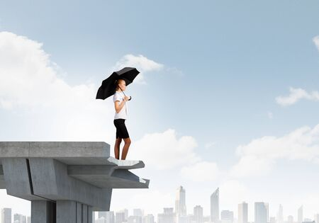 Image of businesswoman standing at the edge of bridge  Risk concept photo
