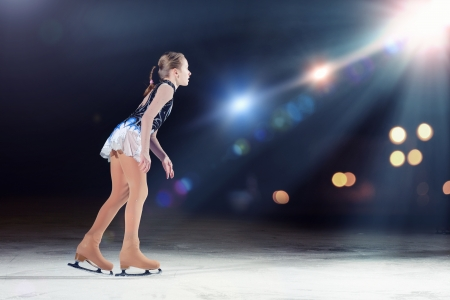 champion: Little girl figure skating at sports arena