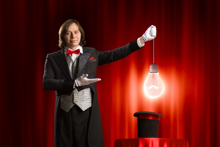 Image of man magician showing trick against color background photo