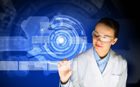 Image of young woman scientist in goggles against media screen photo