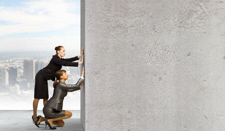 Two businesswoman pushing blank wall  Place for text photo