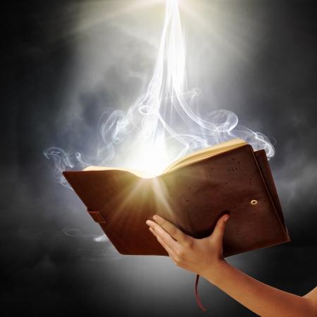 Mano que sostiene el libro de magia humana con luces mágicas Foto de archivo