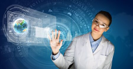 Image of young woman scientist in goggles against media screen  Elements of this image are furnished by NASA photo