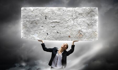 overburdened: Image of young businesswoman holding burden above head Stock Photo