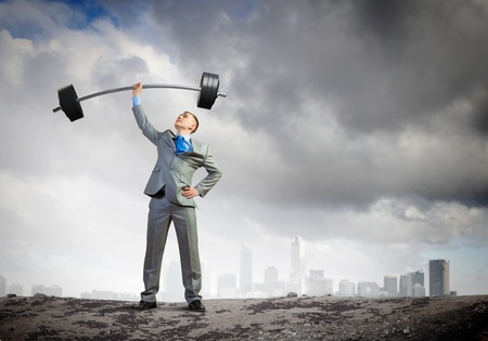 determinism: Image of strong businessman lifting barbell above head with one hand Stock Photo