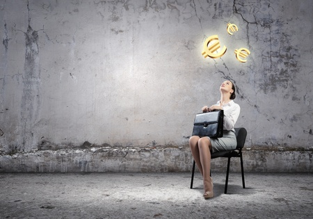 Image de la femme d'affaires assis sur une chaise avec une valise dans les mains regardant symboles de l'euro au-dessus Banque d'images - 22039878