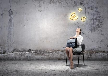 dinero euros: Imagen de la empresaria sentada en la silla con la maleta en las manos mirando por encima de los símbolos del euro Foto de archivo