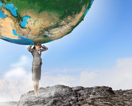 Image of businesswoman holding planet earth on shoulders photo