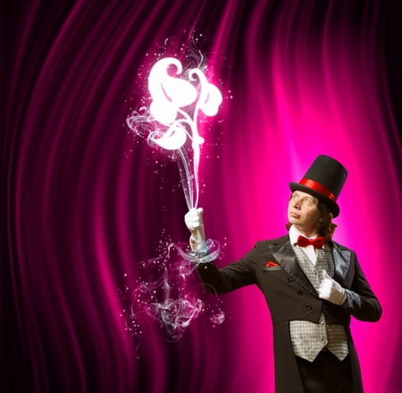 Image of man magician showing trick against color background Stock Photo - 22039929