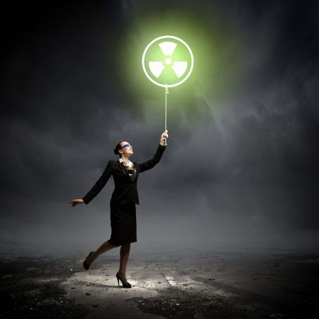 Image of businesswoman in goggles holding balloon with radioactivity symbol photo