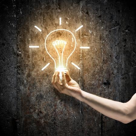 strom: Close up Bild der menschlichen Hand, elektrische Glühbirne in der Dunkelheit