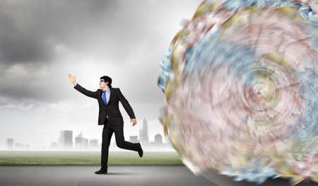Image of businessman trying to run away from money rolling behind photo