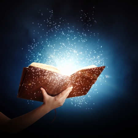 diary page: Human hand holding magic book with magic lights