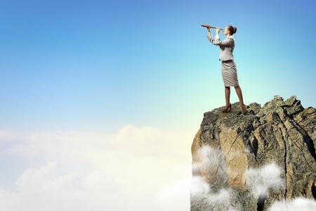 marketanalyze: Image of businesswoman looking in telescope standing atop of rock Stock Photo