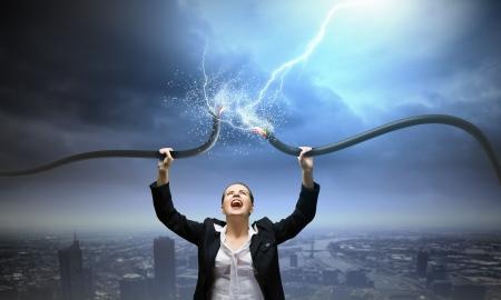 頭の上の電気ケーブルを保持している実業家のイメージ 写真素材