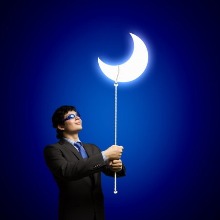 Image of young businessman in goggles looking at moon photo