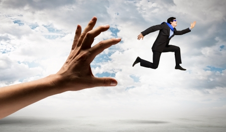 funny image of businessman trying to run away from hand photo