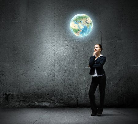 Image of thoughtful businesswoman looking at planet earth photo