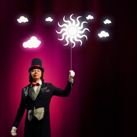 Image of man magician with balloon against color background photo