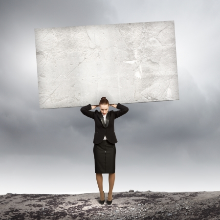 Image of businesswoman holding stone on her shoulders photo