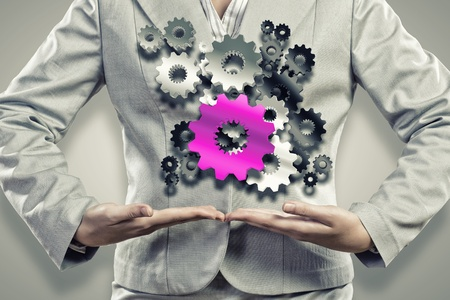 Close up image of businesswoman holding gears in hands photo