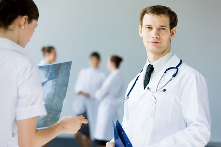 Young doctor in white uniform talking to colleague photo