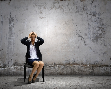 Image of depressed businesswoman sitting on chair photo