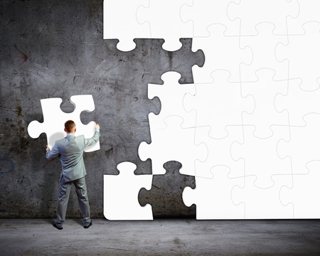 Image of businessman compiling macro white puzzle  Building business photo