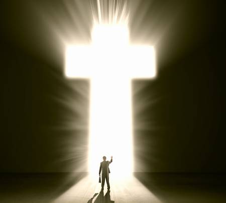 Silhouette of businessman against cross in light Stock Photo - 22071459