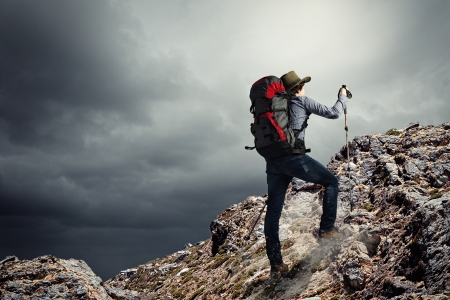 Image of young man mountaineer standing atop of rock photo