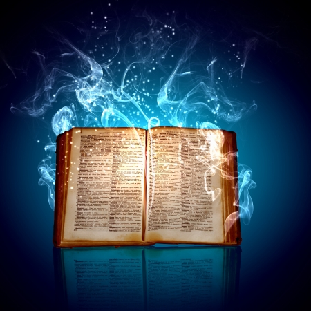 spells: Image of opened magic book with magic lights Stock Photo