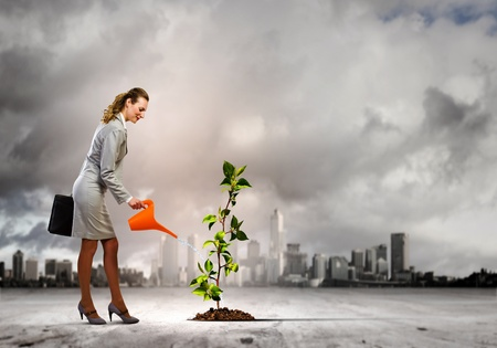 earth handful: Image of businesswoman watering tree with pot  Ecology concept Stock Photo