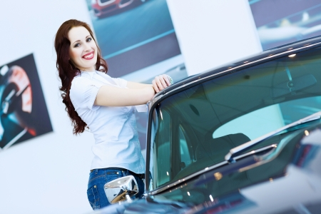 Pretty woman standing near car at car center  Choosing a car photo