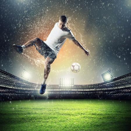 football player in white shirt striking the at the stadium under the rain photo