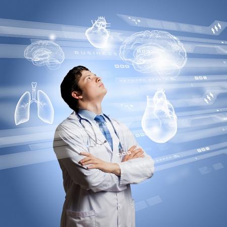 medycyna: Młoda skoncentrowany mężczyzna lekarz z rękami skrzyżowanymi na tle cyfrowych