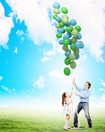 Image of father and daughter playing with bunch of colorful balloons photo