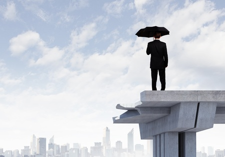 interrupted: Image of businessman with umbrella standing at the edge of bridge