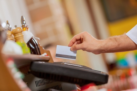Close-up image of cashier male hands holding card photo