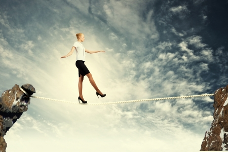 Image of pretty businesswoman balancing on rope photo