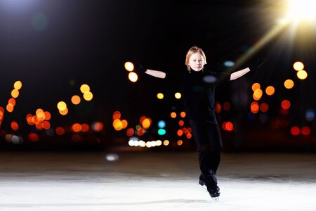 Young boy figure skating at sports arena photo