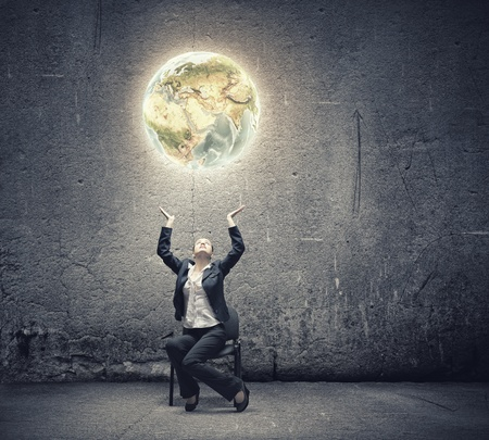 above head: Image of businesswoman holding earth planet in hands above head  Elements of this image are furnished by NASA