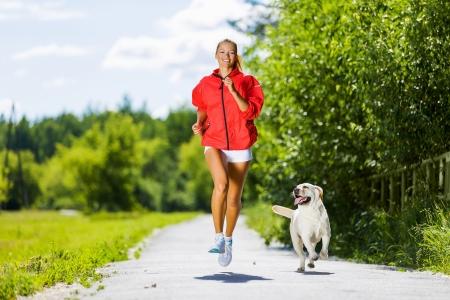 perro labrador: Joven atractiva chica deporte ejecuta con el perro en el parque