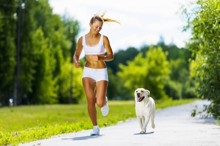 girl jogging: Young attractive sport girl running with dog in park