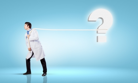 Image of male doctor pulling question sign with rope photo